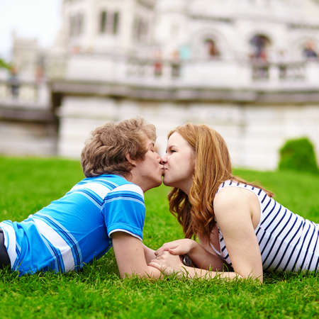 Happy young couple in Paris, near Sacre-Coeur cathedral, lying on the grass and kissing photo