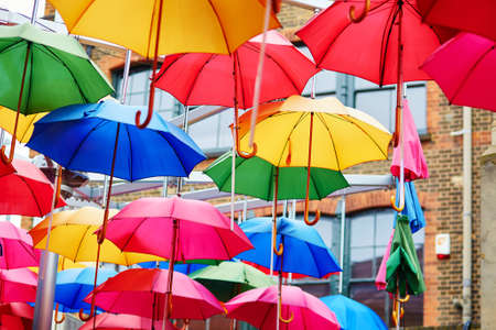 Many colorful umbrellas on a street of London