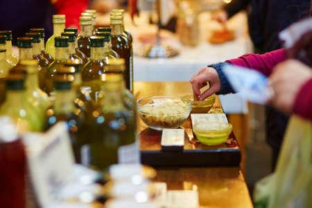 Vrouw degusting verse biologische extra vierge olijfolie op boer landbouwmarkt Stockfoto