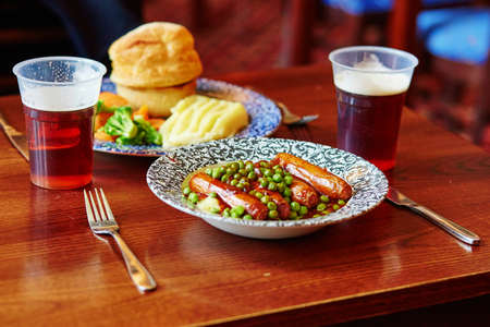 ale: Pork sausages, mashed potatoes, green peas and onion gravy with ale in a traditional English pub