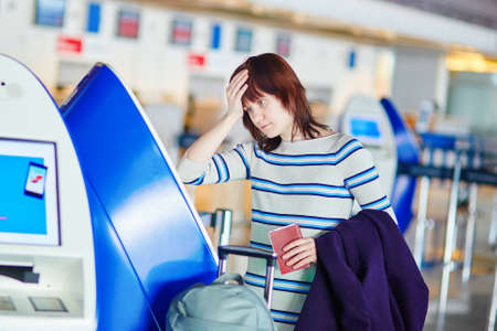 Young female passenger at the airport, doing self check-in, stressed and concerned. Missed, delayed or cancelled flight concept Reklamní fotografie - 39243688