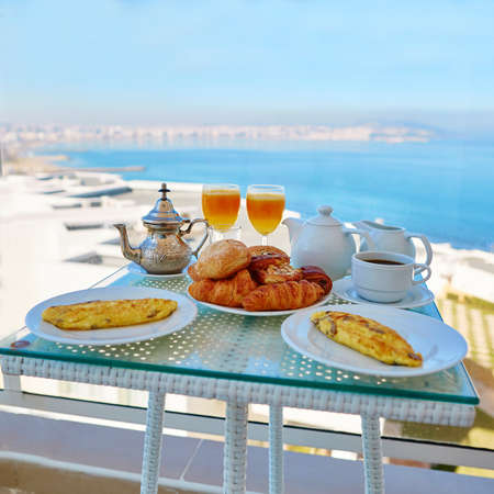 Delicious breakfast with omelet, pastry, coffee and mint tea served on the balcony with sea view in Moroccan hotel Reklamní fotografie