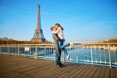 bacio: Romantica coppia divertirsi nei pressi della torre Eifel e baciare