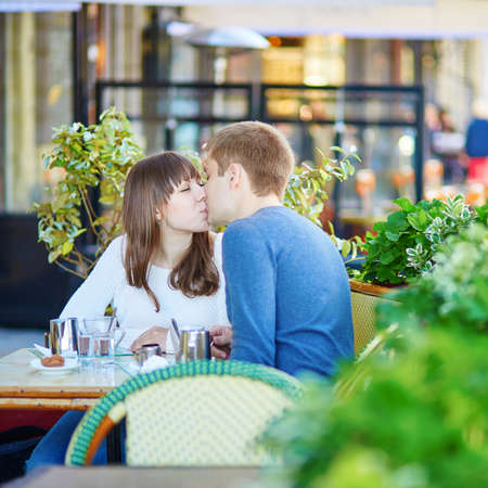 hot date: Young romantic couple having a date in a Parisian outdoor cafe, drinking hot chocolate and kissing Stock Photo