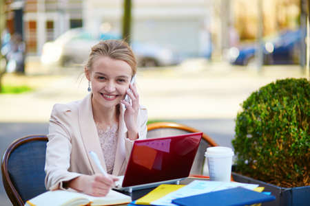 Young businesswoman on a coffee break, using her mobile phone photo