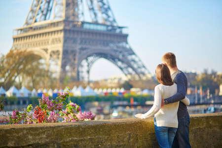 パリのエッフェル塔の近く楽しんでロマンチックなカップル