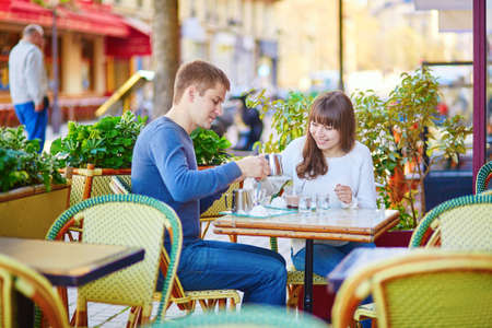 hot date: Young romantic couple having a date in a Parisian outdoor cafe, drinking hot chocolate