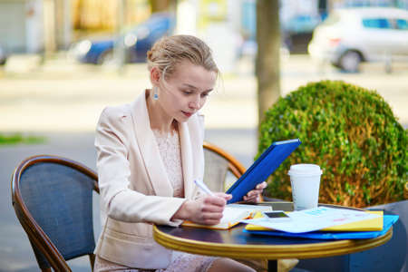 Young businesswoman on a coffee break, working and using her tablet photo