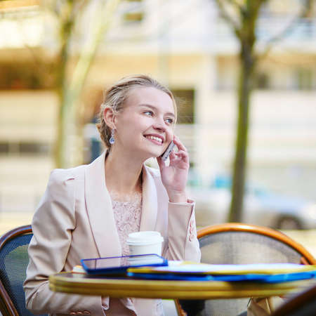 Young businesswoman on a coffee break, working and speaking on the phone photo