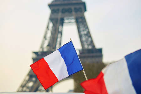 paris: French national flag (tricolour) in Paris with the Eiffel tower in the background