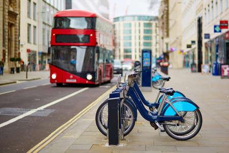 bicicleta: Fila de bicicletas en alquiler con rojo autobús de dos pisos en el fondo en una calle de Londres, Reino Unido