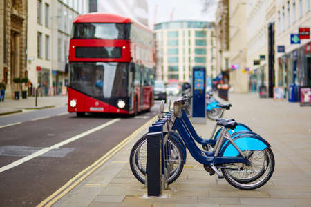 london street: Row of bicycles for rent with red double-decker bus in the background on a street of London, UK