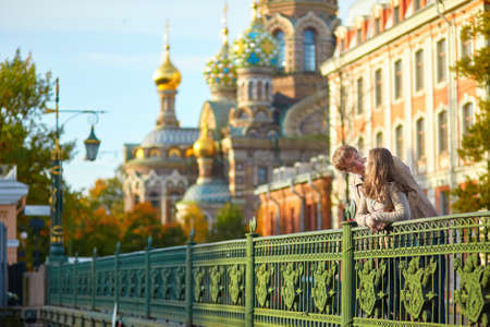 romantic couple: Happy young romantic couple walking together in St. Petersburg, Russia on a warm sunny autumn day near the Church of the savior on Blood