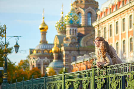 people in church: Happy young romantic couple walking together in St. Petersburg, Russia on a warm sunny autumn day near the Church of the savior on Blood