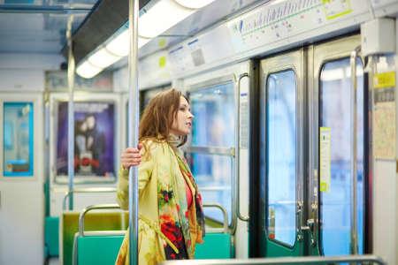 Belle jeune femme parisienne voyager dans une rame de métro, debout près de la fenêtre Banque d'images