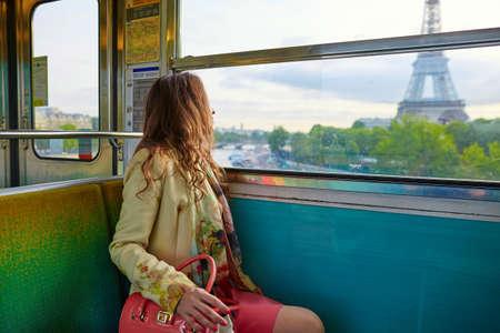 estacion de tren: Mujer hermosa joven parisino que viaja en un tren subterráneo, sentado cerca de la ventana y mirando a la torre Eiffel Foto de archivo