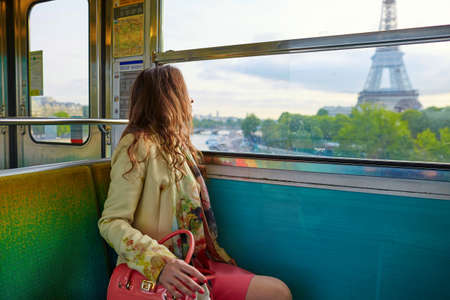 Young beautiful Parisian woman travelling in a subway train, sitting near the window and looking at the Eiffel tower
