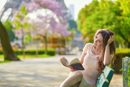 nice day: Beautiful young woman in Paris, near the Eiffel tower on a nice and sunny spring day, reading on the bench outdoors Stock Photo