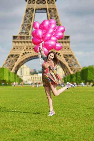 pink balloons: Beautiful young woman in Paris, near the Eiffel tower jumping happily with huge bunch of pink balloons