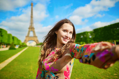 traveller: Woman tourist at Eiffel Tower smiling and making travel selfie. Beautiful European girl enjoying vacation in Paris, France