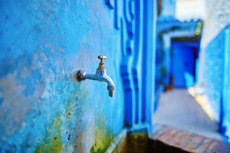 Small fountain with drinkable water on a street in Medina of Chefchaouen, Morocco