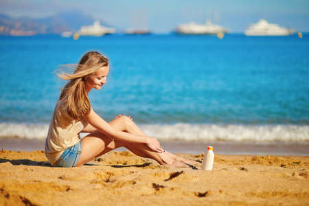 body lotion: Beautiful young woman applying sunscreen on her legs