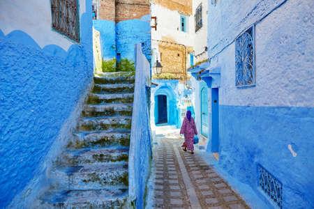 モロッコの女性の伝統的な衣服 (jellaba) モロッコ、シャウエン メディナの青い建物の知られている北西のモロッコの小さな町の路上を歩いて