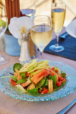 champagne glass: Delicious salad with smoked salmon and prawns served with glass of champagne in a beach restaurant Stock Photo
