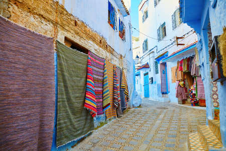 berber: Many colorful Moroccan carpets for sale on a street in Medina of Chefchaouen, Morocco, small town in northwest Morocco known for its blue buildings