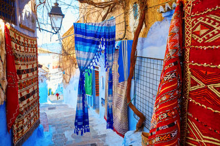 carpet: Many colorful Moroccan carpets for sale on a street in Medina of Chefchaouen, Morocco, small town in northwest Morocco known for its blue buildings