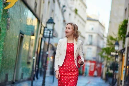 polka dot dress: Beautiful young woman in red polka dot dress walking on a Parisian street