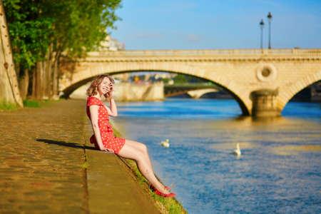 polka dot dress: Beautiful young woman in red polka dot dress near the Seine in Paris