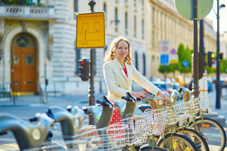 polka dot dress: Beautiful young woman in red polka dot dress taking a bicycle for rent in Paris Stock Photo