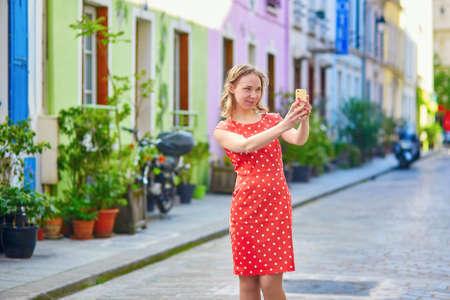 polka dot dress: Beautiful young woman in red polka dot dress taking selfie on a Parisian street