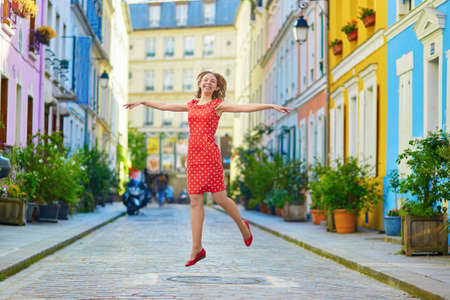 polka dot dress: Beautiful young woman in red polka dot dress jumping on a Parisian street with colorful bright houses Stock Photo
