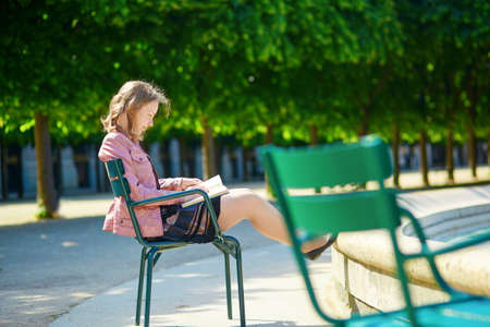 royale: Mujer joven hermosa parisina o estudiante lee un libro en el jard�n Palais Royale