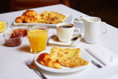 Delicious breakfast with fresh fruits, orange juice, pastry, pancakes and coffee served for two photo