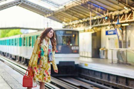 Belle jeune femme parisien dans une station de métro, attendant son train sur la plate-forme Banque d'images