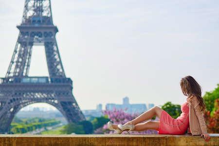 Beau et élégant jeune femme parisienne en robe rose sur les talons hauts assis près de la tour Eiffel à Paris