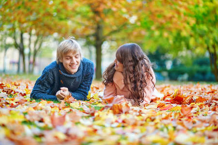 Young dating couple in Paris on a bright fall day lying on the ground in autumn leaves photo
