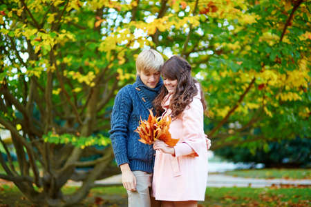 Young dating couple in Paris on a bright fall day gathering autumn leaves photo
