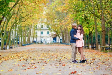 Young dating couple in the Luxembourg gardens of Paris on a bright fall day photo
