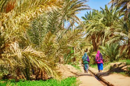 merzouga: Two berber women in national clothes walking in oasis of Merzouga village in Sahara desert, Morocco