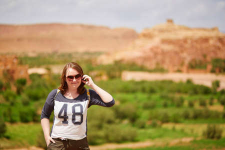 girl glasses: European tourist in picturesque mountain village (kasbah) Ait Ben Haddou not far from Ouarzazate in Morocco, Africa