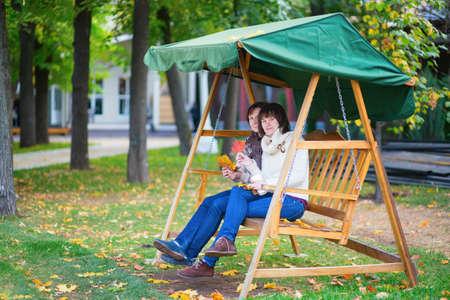 Midden oude vrouw met haar volwassen dochter op een schommel op een daling van de dag, met bladeren in hun handen