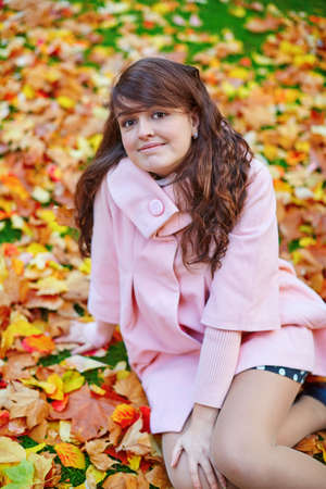 jardin de luxembourg: Beautiful young woman on a bright fall day sitting on the ground covered with fallen autumn leaves Stock Photo