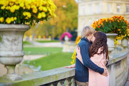 Young dating couple in the Luxembourg gardens of Paris on a bright fall day, kissing photo