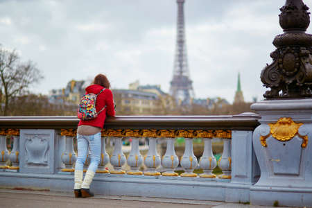 alexandre: Beautiful young tourist in Paris on the Pont Alexandre III, looking at the Eiffel tower Stock Photo
