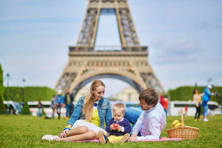 apples basket: Happy family of three, mother, father and little toddler boy, having picnic in Paris near the Eiffel tower