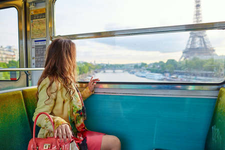 Beautiful young woman travelling in a train of Parisian underground and looking through the window at the Eiffel tower